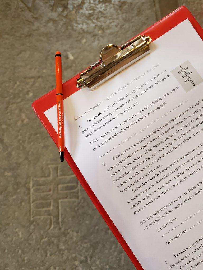 Zdjęcie w Centrum św. Jana. Zbliżenie na podkładkę piśmienniczą z kartą zadań dotyczących wyposażenia kościoła. W tle widoczna płyta nagrobna z gmerkiem kościoła św. Jana.